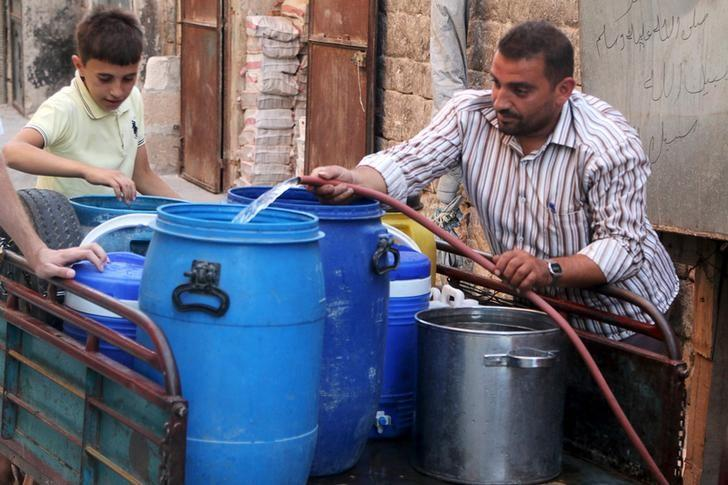Residents fill containers with water in a rebel-controlled area of Aleppo, Syria